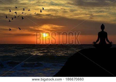Woman silhouette meditating in a yoga pose on the beach at sunrise