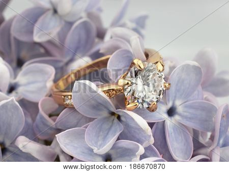Ring with diamond on violet flower soft focus