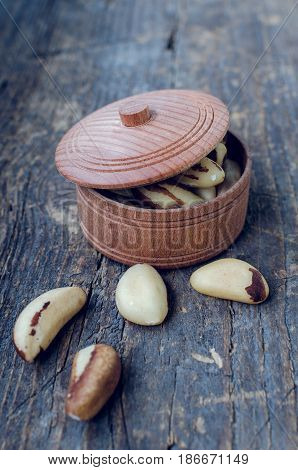 Tasty Brazil nuts from Bertholletia excelsa tree in wooden bowl on the old background. Healthy edible seeds food ingredient on the table.