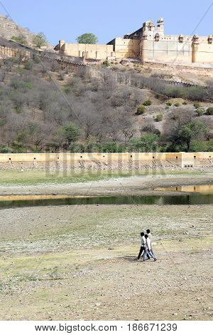 Men walking on dry lake bed in front of Amer Fort