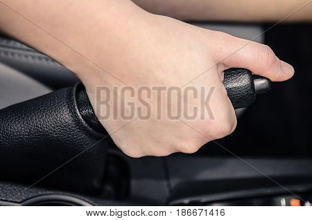 Hand pulling the car handbrake. Car interior.
