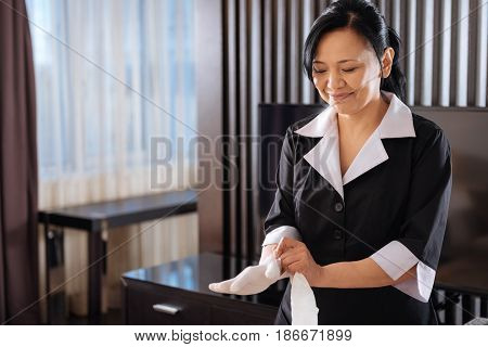Sanitation norms. Nice pleasant delighted hotel maid wearing disposable gloves and looking at her hands while preparing to start cleaning