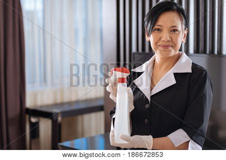 Room cleaning service. Positive Asian nice hotel maid holding a cleaning agent and looking at you while cleaning the hotel room