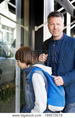 Father and son near showcase, boy looks inside shop with interesting and man looking at camera