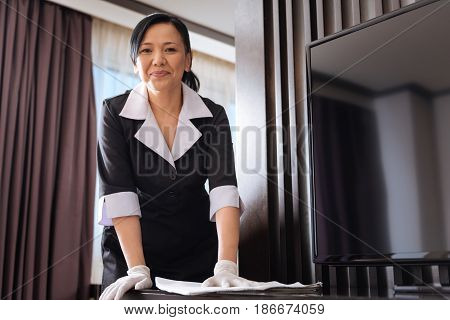 Clean table. Hard working nice Asian hotel maid holding a duster and wiping the dust from the table while doing the cleaning up
