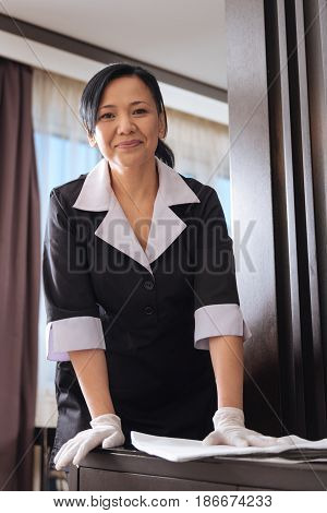 Wipe off the dust. Pleasant nice Asian woman standing in the hotel room and using a duster while cleaning the table