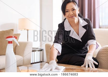 Time for cleaning. Joyful pleasant professional hotel maid sitting in the armchair and smiling while cleaning the table