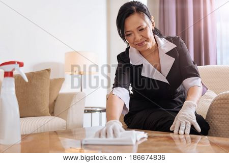 Professional hotel maid. Nice positive Asian woman holding a duster and cleaning the table while concentrating on her job