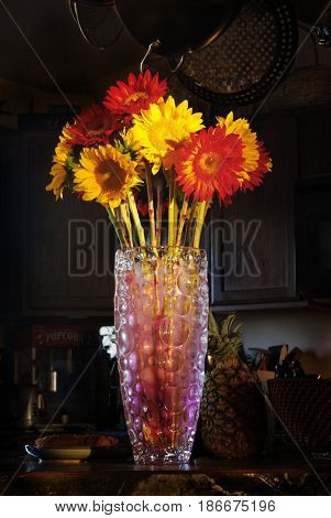 Vase of red and yellow sunflowers in kitchen highlighted by afternoon sun