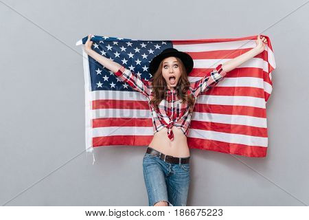 Portrait of an excited young woman holding USA flag and looking at camera isolated over gray background