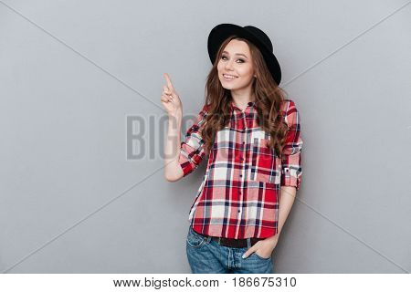 Portrait of young cheerful girl in plaid shirt pointing finger up at copyspace isolated over gray background