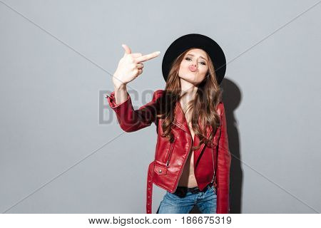 Picture of young angry woman standing over grey wall wearing hat showing middle finger. Looking at camera.