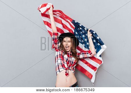 Portrait of a happy excited girl holding USA flag isolated over gray background