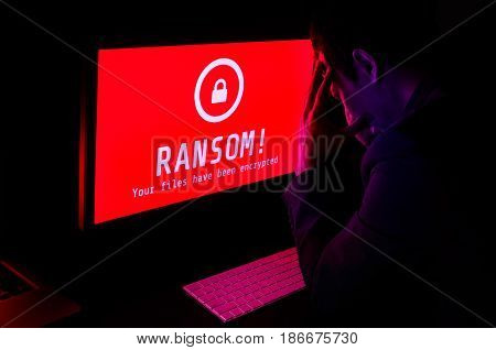 Computer screen with ransomware attack file encrypted alerts in red and a man in suit get stress with keyboard in a dark room ideal for online security failure and digital crime long exposure selective focus