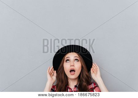 Portrait of a shocked young woman in hat looking up at copyspace isolated over gray background