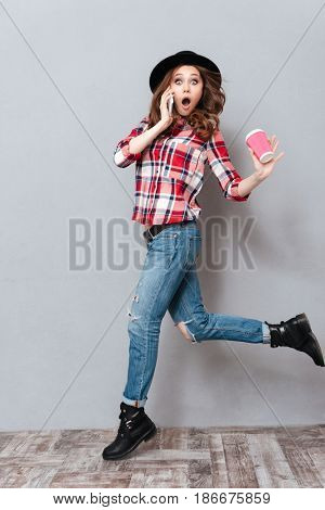 Full length portrait of a surprised pretty girl in plaid shirt talking on mobile phone and holding coffee cup to go while running isolated over gray background