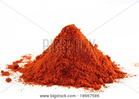 a one pile of ground paprika on white, bright red color, sharp shot.