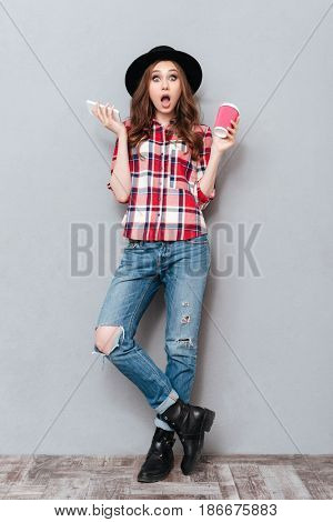Full length portrait of a shocked stunned girl in plaid shirt holding mobile phone and coffee cup to go isolated over gray background