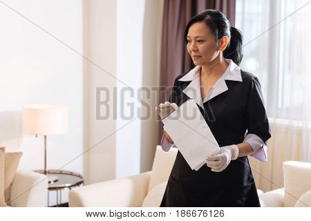 Looking for dust. Positive nice delighted hotel maid standing in the hotel room and looking around it while holding a duster