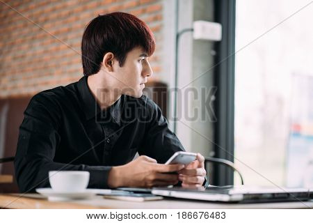 Male sitting at the table with laptop and cup of coffee looking through a window