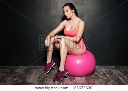 Picture of amazing sportswoman sitting over grey background on ball. Looking aside.