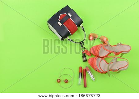 Stylish woman red Handbag and cosmetics,makeup accessories on green background
