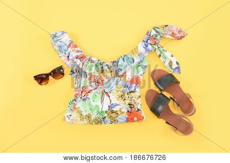 Fashion. Summer woman accessories-Summer floral clothes, shoes,sunglasses  on yellow background