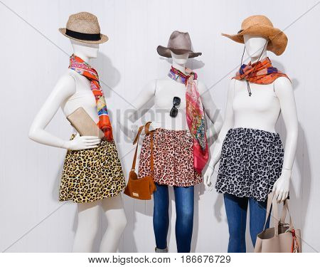 three female in jeans clothing with hat and scarf ,sunglasses ,handbag on mannequin