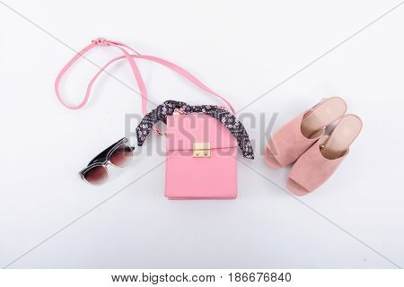 Fashion concept. Pink handbag , shoes ,sunglasses on a white background