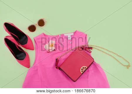 Fashion concept. handbag , red shoes ,sunglasses ,clothes on a green background