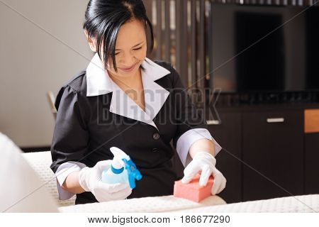 Professional service. Joyful nice delighted hotel maid sitting on the sofa and cleaning it while doing the room service