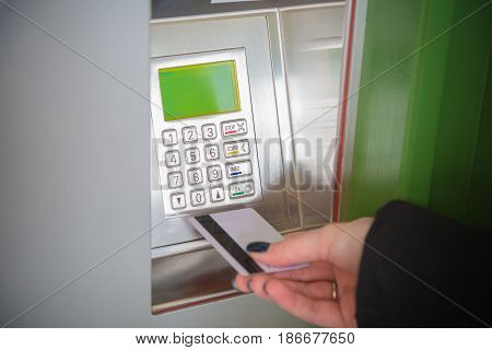 Close up of female hand holding ATM card next to the bank machine to withdraw money