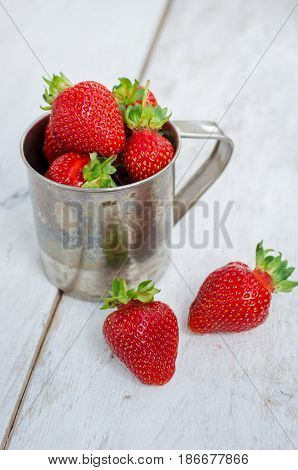 Red berry strawberry in metal mug on white rustic wooden background. Background from freshly harvested strawberries. Strawberry background. Selective focus. Shallow depth of field. Vertical.
