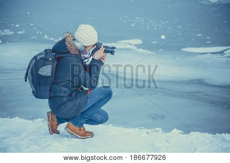 Portrait of female photographer shooting winter landscape next to the frozen lake.
