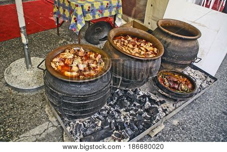 Cooking pork stew in a traditional way in a clay pot.