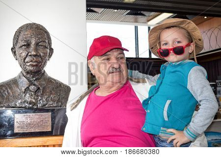 CAPE TOWN SOUTH AFRICA - 19 December 2016 - Illustrative Editorial Image of a white South African grandfather and grandson standing next to the bronze bust of Nelson Mandela anti-apartheid freedom fighter and ex president of South Africa - Conceptual Imag