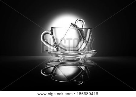 Two transparent tea cups made of glass on a table with reflection. Black and white kitchen items. Without liquid. One cup is on top of the other.