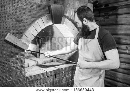 Male Baker cooking oven for cooking and stirred the coals with the poker.