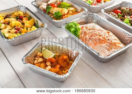 Healthy daily meals delivery concept. Fruits and salads in foil containers on white wood background
