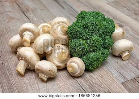 Broccoli and mushrooms champignons close-up on a wooden board. Horizontal photo.