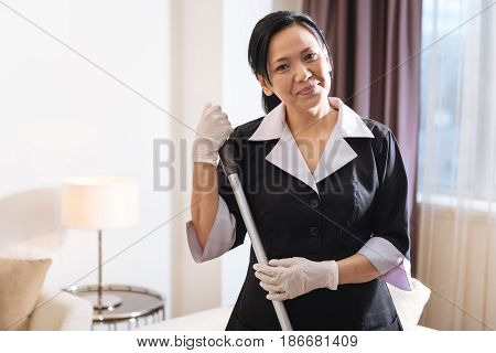 Hotel service. Delighted positive nice chambermaid looking at you and smiling while cleaning the floor