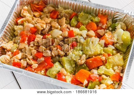 Healthy eating, diet concept. Take away organic food. Weight loss nutrition in foil boxes. Chopped steamed beef and vegetables closeup