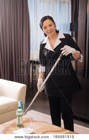 In the hotel room. Nice serious pleasant hotel maid holding a mop and cleaning the floor while doing her duties