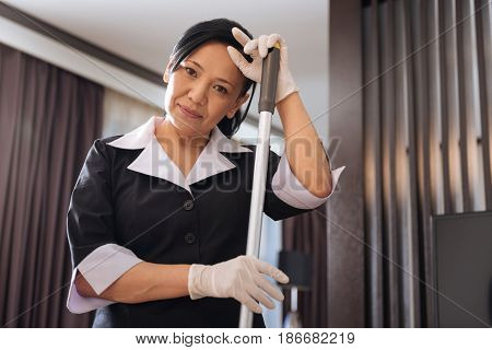 Hard working woman. Positive professional delighted chambermaid holding a mop and looking at you while cleaning the hotel room