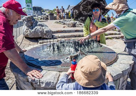 CAPE TOWN SOUTH AFRICA 18 December 2016: Tourists and visitors admiring the bronze outline 3D moulding of Table Mountain on top of Table Mountain Cape Town South Africa - Illustrative editorial image