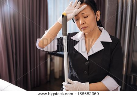 Too much work. Pleasant nice exhausted chambermaid holding a mop and trying to rest while feeling tired