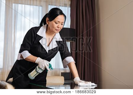 Absolute tidiness. Serious hard working professional chambermaid using a cleansing spray and making the table clean while working in the hotel room