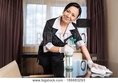 On the way to cleanness. Joyful good looking positive chambermaid holding a duster and using the cleansing spray while wiping the table