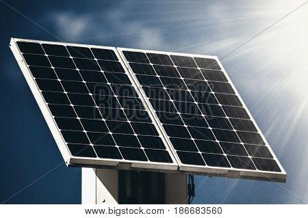 Solar panel and sun beams against the blue sky