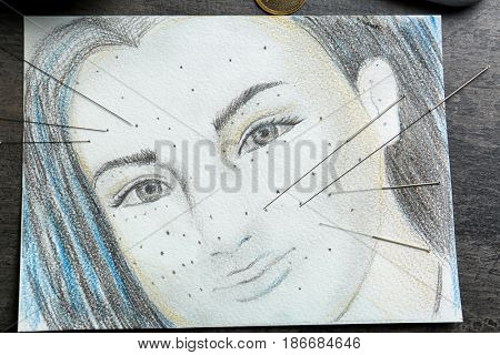Acupuncture needles and portrait drawing, closeup